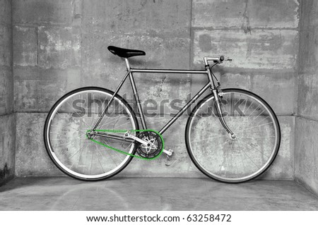 A fixed-gear bicycle (also called fixie) in black and white with a green chain - stock photo