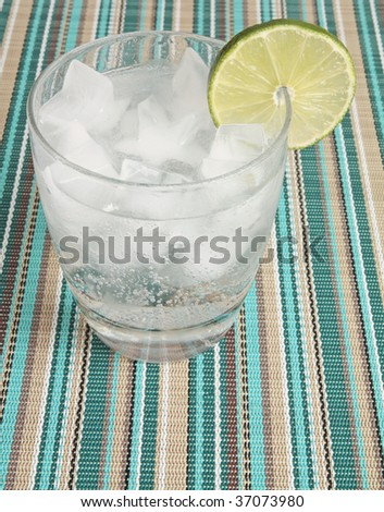 A fizzy mixed drink garnished with a lime sits on a summery placemat - stock photo