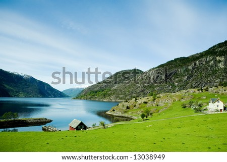 A fjord and rural norway with a blue sky - stock photo
