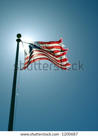 a flag waving in the breeze with the sun illuminating it from behind