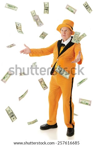 A flamboyant senior man wearing an orange tuxedo and hat, tossing or catching falling 100, 50 and 20 dollar bills.  On a white background. - stock photo