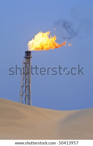 A flare stack burning off excess gas at an oil refinery in the desert - stock photo
