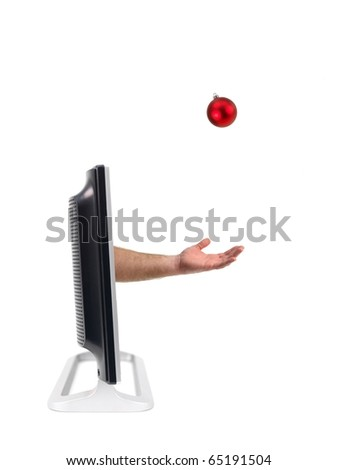 A flat screen tv with a hand reaching for a christmas ornamnt - stock photo