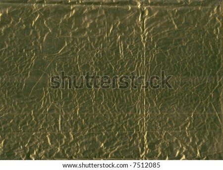 A flattened piece of gold wrapping foil, suitable as a background texture. - stock photo