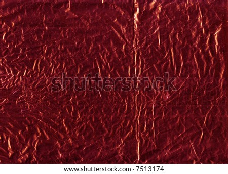 A flattened piece of red wrapping foil, suitable as a background texture. - stock photo