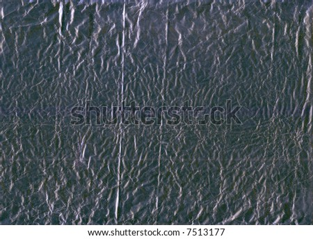 A flattened piece of silver wrapping foil, suitable as a background texture. - stock photo