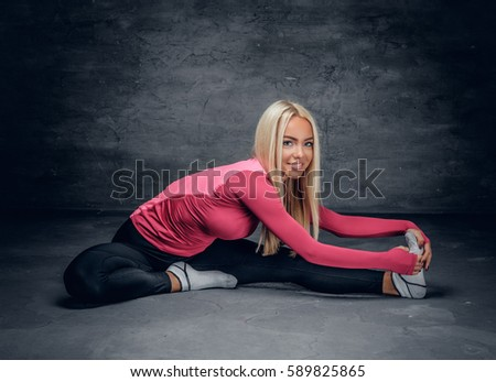 A flexible blond female dressed in a pink jersey sits on a floor.