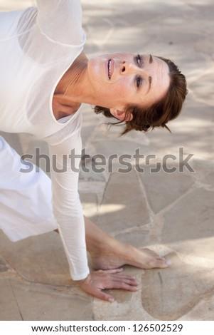 A flexible middle age senior woman doing yoga - stock photo