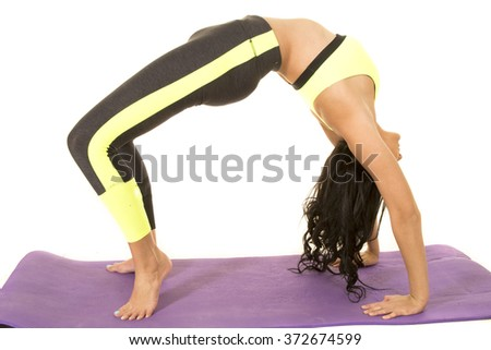 A flexible woman doing a back bend in fitness clothes.