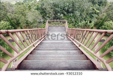 A flight of steps descending onto an aging timber observation deck overlooking a tropical rainforest canopy. - stock photo