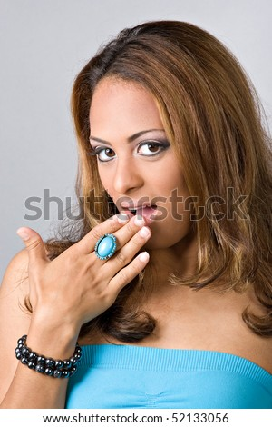 A flirty Spanish woman covering her mouth out of surprise. - stock photo
