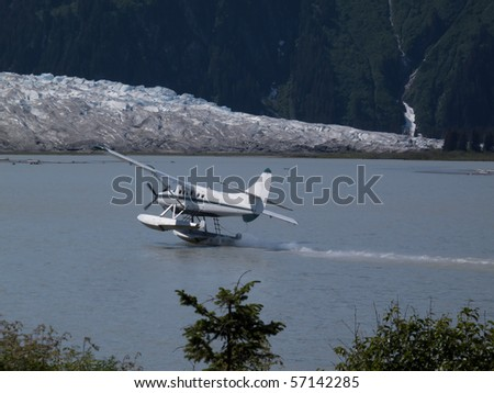 A float plane taking off on the ocean to fly over a mountain and a big glacier. - stock photo