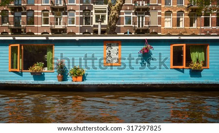 A floating house with open windows painted in aqua-orange colors on the water of the canal - stock photo
