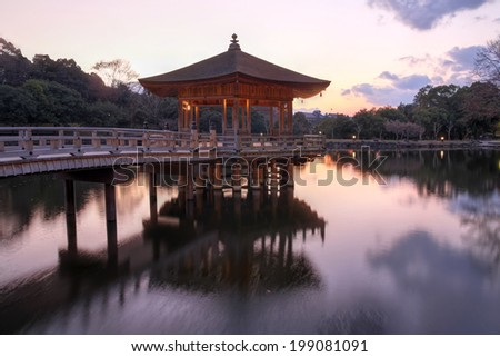 A floating pavilion in Nara Park, the ancient capital of Japan on a background of the setting sun. - stock photo