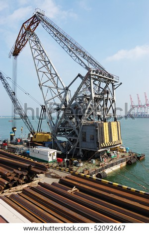 A floating platform with a crane, materials and equipment to strengthen the coast