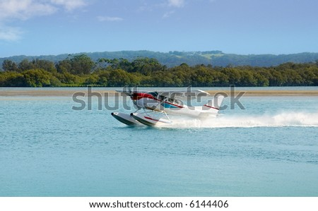 A floating Seaplane speeds up to take off on a sightseeing excursion on the New South Wales Coast, Australia - stock photo