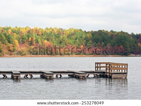 A floating wood dock in a small lake on a semi-cloudy Autumn day.