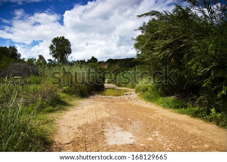 A flooded gravel road - stock photo