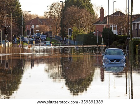A flooded road junction with a drowned car - stock photo
