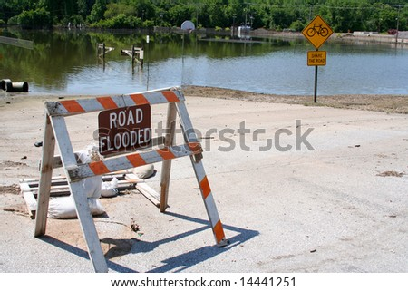 A Flooded Road sign stands before roads and a basketball court swimming with water. - stock photo