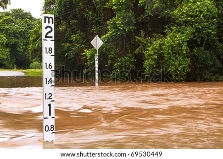 A flooded road with depth indicators in Queensland, Australia - stock photo