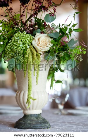 A floral wedding centerpiece on a table during a catered event - stock photo