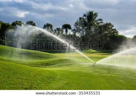 a florida golf green being irrigated with reclaimed water in the morning