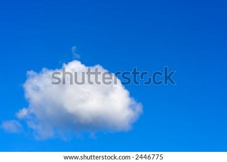 A fluffy white cumulus cloud against a blue sky - stock photo