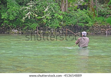 a fly-fisherman casts a fly across a swift river towards the far bank, while wading in deep water - stock photo