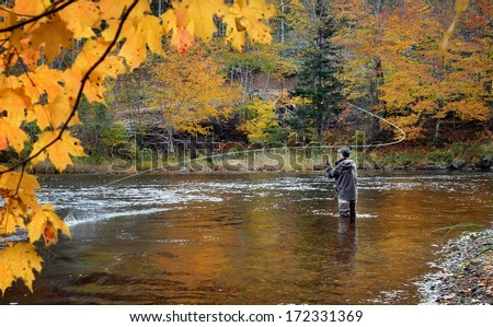 A fly fisherman fishing for Atlantic Salmon on the Margaree River in the fall. - stock photo