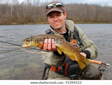 A fly fisherman posing with a Brown Trout with his fly rod and reel, before releasing the fish into the river - stock photo