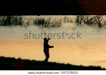 A flyfisherman besides a lake at dusk. - stock photo