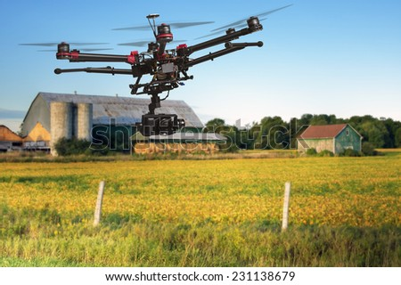 A flying helicopter with raised landing gears and a camera with blurred crop field and farm structures on a background highlighted by a sunset - stock photo