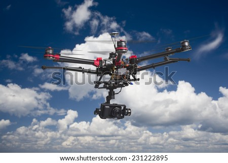 A flying multicopter with raised landing gears and a camera in beautiful cloudy skies - stock photo
