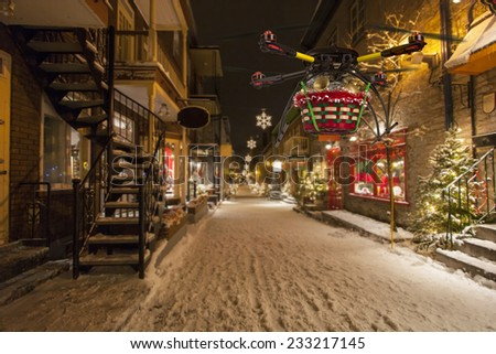 A flying quadrocopter delivering a basket of Christmas goodies above covered with snow beautifully decorated street - stock photo