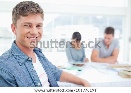 A focused shot on a student looking into the camera and smiling with his friends working in the background - stock photo