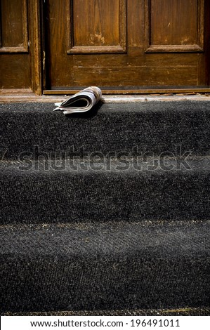A folded newspaper laying in front of a door. - stock photo