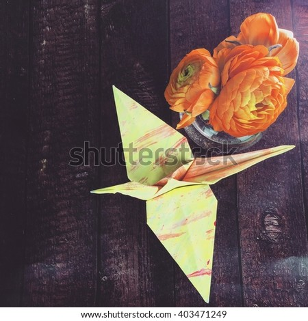 A folded origami crane on dark wooden table with tree small orange ranunculus flowers. - stock photo