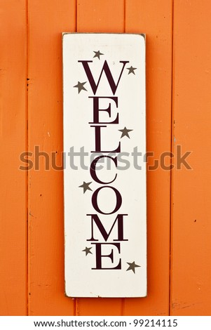 A folksy styled wooden 'Welcome' sign on the side of a brightly colored wooden building. - stock photo