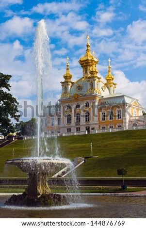 A fontain and a church against blue sky. Peterhof, Russia - stock photo