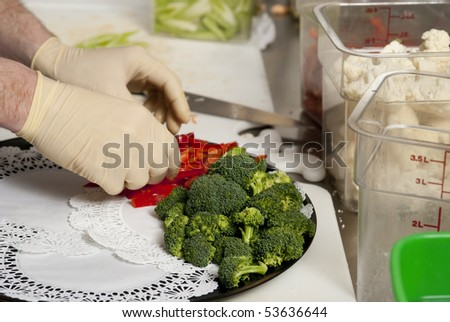 A food service worker places broccoli on a tray