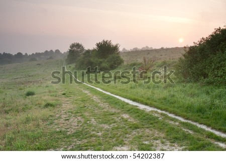 A foopath on Pewley Down at sunrise in May.  Pewley Down is part of the North Downs in Surrey which is an Area of Outstanding Natural Beauty. - stock photo