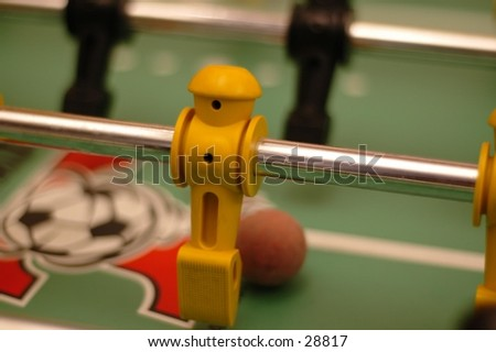 "A foosball ""player"" gets ready to kick the ball. - stock photo"