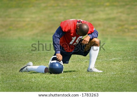 A footbal player down on one knee. Praying. - stock photo