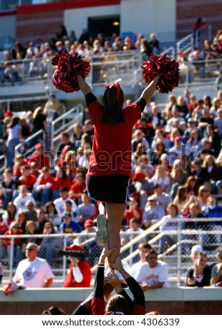 A football cheerleader is raised into the air in front of a large collegiate crowd. - stock photo
