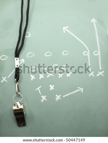 A football diagram on a chalkboard showing the sweep with a coaches whistle. - stock photo