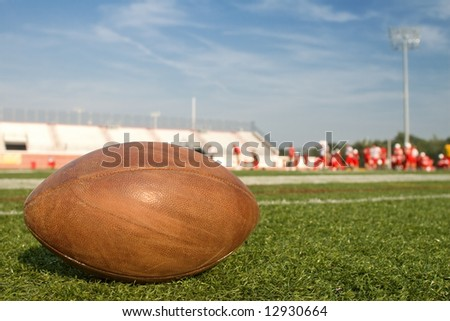 A football is the focal point, as a college team practices. - stock photo