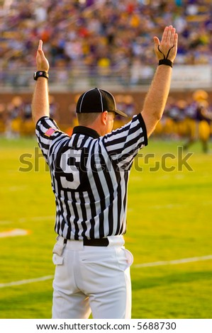 A Football Official signaling football and a game of American Football - stock photo