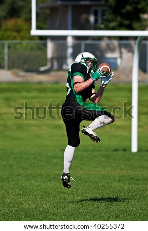 A football player leaping off the ground, to catch the ball near the goal posts. - stock photo