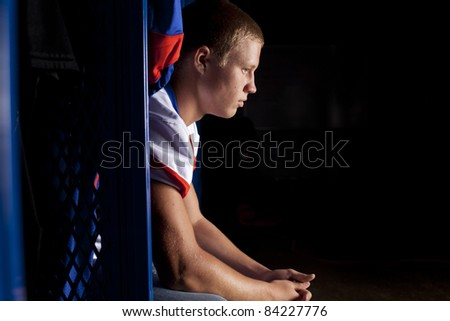 A football player sits in his locker thinking about the game. - stock photo